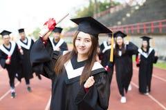 Lyckliga avläggande av examenstudenter med diplom utomhus Arkivbilder