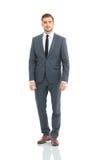 Lyckliga bärande grå färger för affärsman passar anseende- och vikningarmar royaltyfri foto
