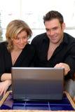 lyckliga bärbar datorpar royaltyfria bilder
