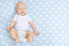 Lyckliga Baby som ligger på blått, mattar bakgrund som ler den begynnande ungen arkivbild