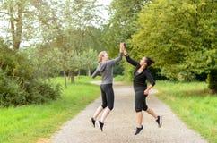 Lyckliga banhoppningkvinnor som gratulerar sig arkivbilder