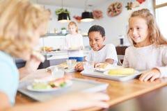 Lyckliga barn äter i kantin Royaltyfria Foton