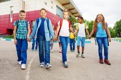 Lyckliga barn bär ryggsäckar, går nära skola fotografering för bildbyråer