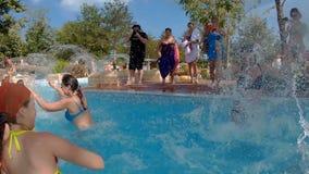 Lyckliga barn badar och plaskar i pölen lager videofilmer