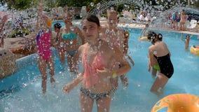 Lyckliga barn badar och plaskar i pölen stock video