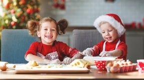 Lyckliga barn bakar julkakor royaltyfri bild