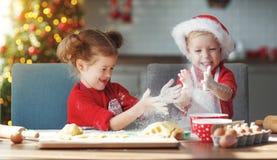 Lyckliga barn bakar julkakor fotografering för bildbyråer