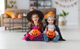 Lyckliga barn i dräkter av häxan och vampyren förbereder sig arkivfoto