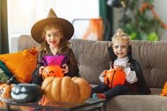 Lyckliga barn i dräkter av häxan och vampyren förbereder sig arkivfoton
