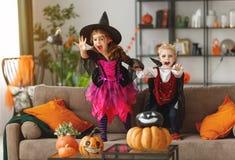 Lyckliga barn i dräkter av häxan och vampyren förbereder sig arkivbild