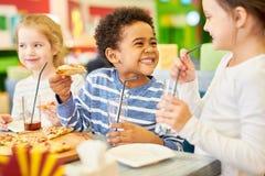 Lyckliga barn i pizzeria arkivfoto