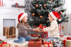 Lyckliga barn i santa hattar som packar upp julgåvor Arkivfoton