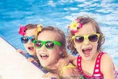 Lyckliga barn i simbassängen arkivbild