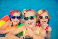 Lyckliga barn i simbassängen arkivfoto