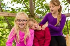 Lyckliga barn i trädgården och skratt Arkivfoto