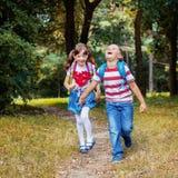 Lyckliga barn kör med ryggsäckar från skola fyrkant T arkivbild