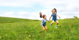 Lyckliga barn kopplar samman systrar som hoppar och skrattar i sommar Arkivfoto