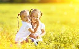 Lyckliga barn kopplar samman systrar som omfamnar i sommar på naturen Royaltyfri Foto