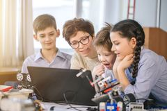 Lyckliga barn lär att programmera genom att använda bärbara datorer på extracurricular grupper royaltyfri fotografi