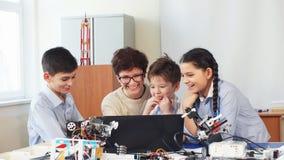 Lyckliga barn lär att programmera genom att använda bärbara datorer på extracurricular grupper lager videofilmer