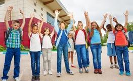 Lyckliga barn med armar upp att stå nära skola royaltyfri foto