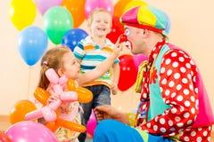 Lyckliga barn med clownen på födelsedagdeltagare royaltyfri bild