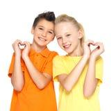 Lyckliga barn med en underteckna av hjärta formar Royaltyfri Bild