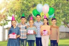 Lyckliga barn med gåvor på födelsedagpartiet Arkivfoto