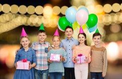 Lyckliga barn med gåvor på födelsedagpartiet royaltyfria foton