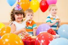 Lyckliga barn med gåvor på födelsedagdeltagare Arkivfoton