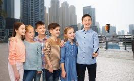 Lyckliga barn med smartphonen och selfiepinnen Arkivbild