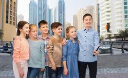 Lyckliga barn med smartphonen och selfiepinnen Royaltyfri Bild
