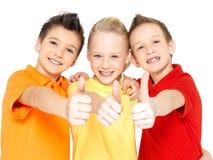 Lyckliga barn med tum göra en gest upp Royaltyfria Bilder