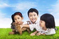 Lyckliga barn med valpen Arkivfoton