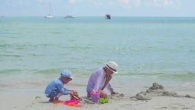 Lyckliga barn och hund som spelar på den sandiga stranden med leksaker Tropisk ö, på en varm dag stock video