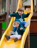 Lyckliga barn på glidbana på lekplatsen Royaltyfri Bild