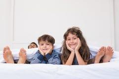 Lyckliga barn på säng Arkivfoton