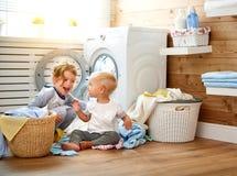 Lyckliga barn pojke och flicka i tvätteri laddar tvagningmaskinen Royaltyfria Foton