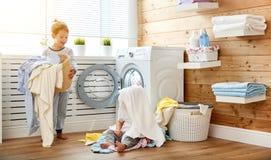 Lyckliga barn pojke och flicka i tvätteri laddar tvagningmaskinen Royaltyfri Bild
