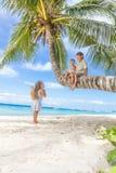 Lyckliga barn - pojken och flickor - på palmträdet som är tropisk Arkivfoton