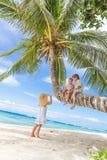 Lyckliga barn - pojken och flickor - på palmträdet som är tropisk Royaltyfria Foton
