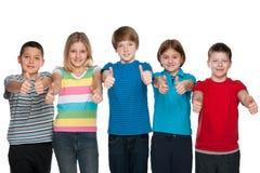 Lyckliga barn rymmer upp deras tummar Arkivbild