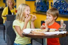 Lyckliga barn som äter inomhus att le för pizza arkivbilder