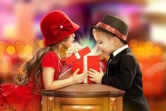 Lyckliga barn som öppnar den magiska gåvan Arkivfoto