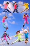 Lyckliga barn som övar och hoppar i den blåa himlen arkivfoto