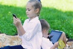 Lyckliga barn som använder den minnestavlaPC och smartphonen royaltyfri bild
