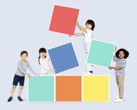 Lyckliga barn som bygger färgrika kvarter royaltyfri bild