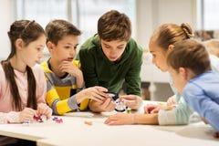 Lyckliga barn som bygger robotar på robotteknikskolan royaltyfria bilder