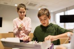 Lyckliga barn som bygger robotar på robotteknikskolan Royaltyfri Foto