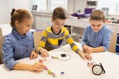 Lyckliga barn som bygger robotar på robotteknikskolan Arkivbild
